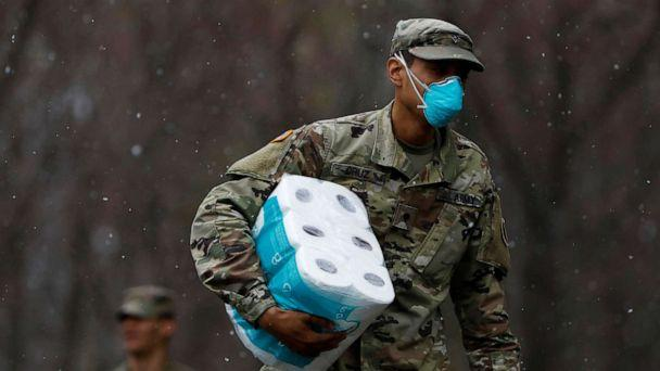 PHOTO: A member of Joint Task Force 2, composed of soldiers and airmen from the New York Army and Air National Guard, wears a face mask while carrying paper towels during the coronavirus outbreak in New Rochelle, N.Y., March 23, 2020.  (Andrew Kelly/Reuters)