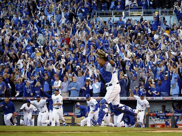 Fans cheer as Kansas City Royals catcher Salvador Perez celebrates after the Royals defeated the Baltimore Orioles 2-1 in Game 4 of the American League baseball championship series Wednesday, Oct. 15, 2014, in Kansas City, Mo. The Royals advance to the World Series. (AP Photo/Matt Slocum )