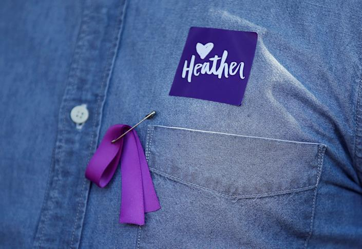 A man wears a purple ribbon to remember Heather Heyer, who was killed protesting during a white supremacistrally, as he arrives for her memorial service at the Paramount Theater in Charlottesville, Virginia, on Aug.16, 2017.