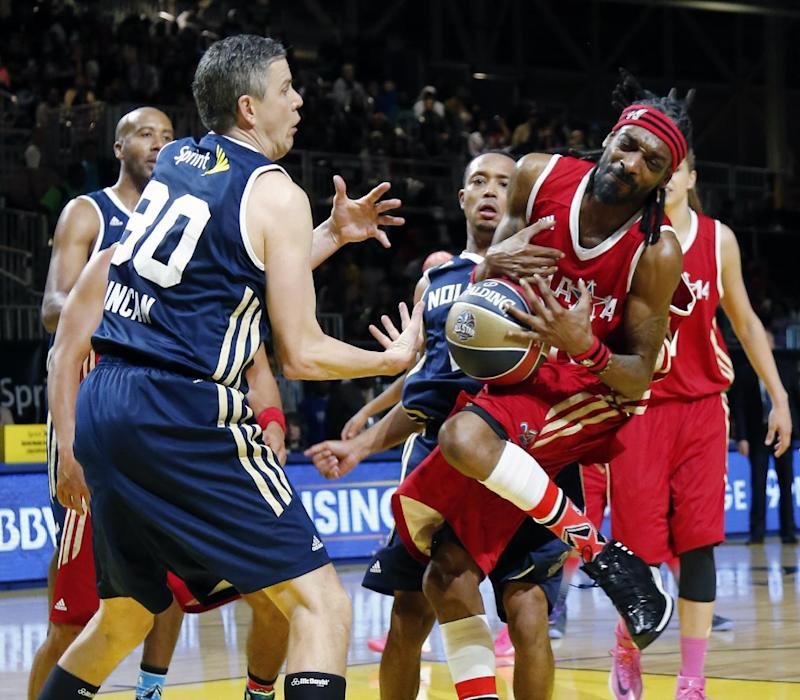 U.S. Education Secretary Arne Duncan, left of the East team struggles with West's Snoop Dogg for a loose ball in the second half of the NBA All-Star Celebrity basketball game in New Orleans, Friday, Feb. 14, 2014. The East won 60-56. (AP Photo/Bill Haber)