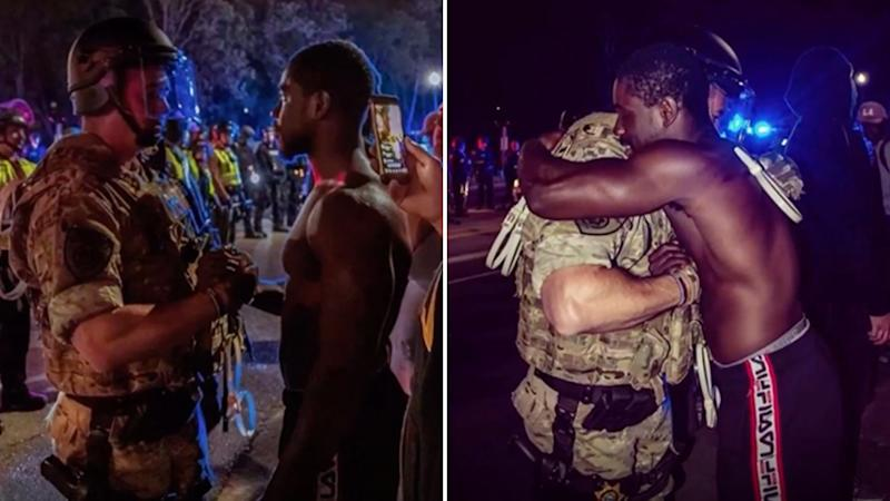 Black protestor Mark Karluah and white police officer David Cate embrace during a protest over George Floyd's death.
