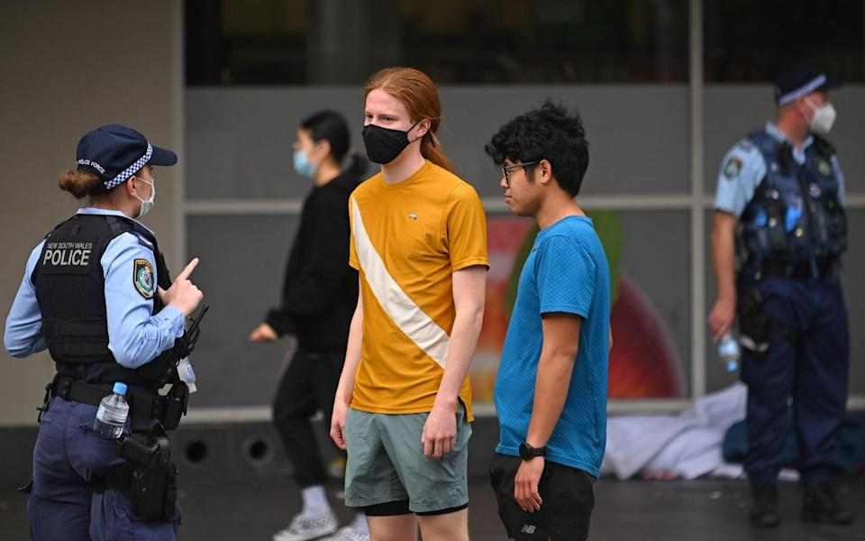 Police officers check ID cards of people walking in the CBD in order to prevent an anti-lockdown protest, during lockdown in Sydney, Australia, Saturday, July 31, 2021. - Anadolu