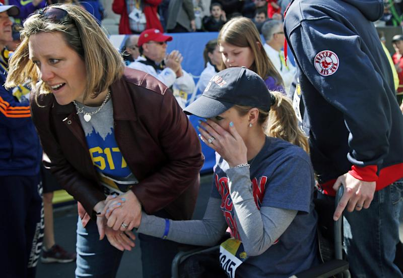 Survivor Rebekah Gregory DiMartino, center, wipes tears as she is led in her wheelchair after crossing the finish line of the Boston Marathon Tribute Run in Boston, Saturday, April 19, 2014. (AP Photo/Elise Amendola)