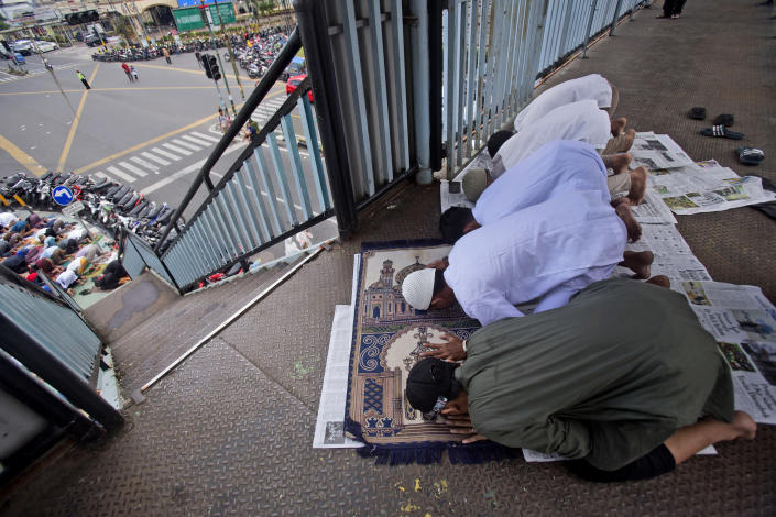 """Muslim youths pray on a pedestrian bridge outside a crowded mosque during an Eid al-Adha prayer in Medan, North Sumatra, Indonesia, Friday, July 31, 2020. Eid al-Adha, or """"Feast of the Sacrifice,"""" is a holiday which honors the prophet Ibrahim, or Abraham, as he is known in the Bible, for his willingness to sacrifice his son on the order of God who was testing his faith. (AP Photo/Binsar Bakkara)"""