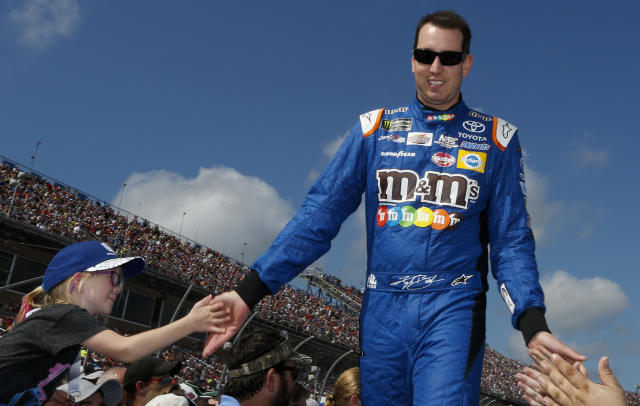 "NASCAR driver <a class=""link rapid-noclick-resp"" href=""/nascar/sprint/drivers/947/"" data-ylk=""slk:Kyle Busch"">Kyle Busch</a> (18) high fives fans as he walks off the stage during the NASCAR Talladega auto race driver introductions at Talladega Superspeedway, Sunday, Oct. 15, 2017, in Talladega, Ala. (AP Photo/Brynn Anderson)"