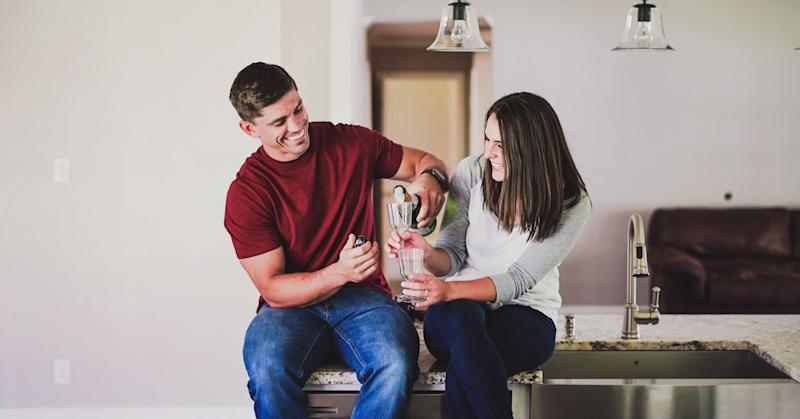 Couple toasting over champagne in new home.