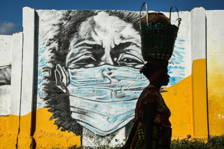 A Tanzanian woman walks in front of a mural painted by the Wachata artists group to raise awareness about avoiding the spread of coronavirus. Magufuli has claimed prayer saved the country from Covid-19