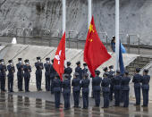Hong Kong police officers attend a flag raising ceremony on the National Security Education Day at a police school in Hong Kong Thursday, April 15, 2021. Authorities marked the event with a police college open house, where police personnel demonstrated the Chinese military's goose step march, replacing British-style foot drills from the time Hong Kong was ruled by the U.K. until the 1997 handover to China.(AP Photo/Vincent Yu)