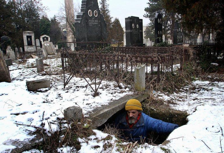 Bratislav Jovanovic enters a grave which he uses as a shelter, in Nis, Serbia, on January 10, 2013. Serbia has an estimated 200,000 homeless people among its population of 7.2 million, according to a rights group survey last year