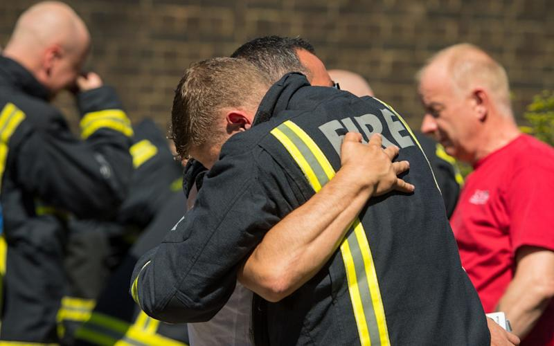 A fighfighter and a man embrace at the Latymer Community Centre, before observing the minute's silence - Credit: Dominic Lipinski/PA Wire