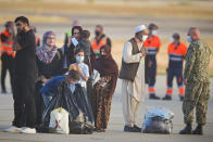 Evacuees from Afghanistan stand on the tarmac after disembarking from a U.S. airforce plane at the Naval Station in Rota, southern Spain, Tuesday Aug. 31, 2021. The United States completed its withdrawal from Afghanistan late Monday, ending America's longest war. (AP Photo/ Marcos Moreno)