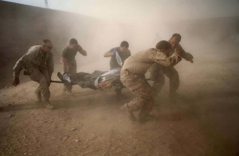 "In this picture taken Tuesday, May 10, 2011, United States Marines run through dust kicked up by a Blackhawk helicopter from Task Force Lift ""Dust Off"", Charlie Company 1-214 Aviation Regiment as they rush a colleague wounded in an IED strike for evacuation near Sangin, in the volatile Helmand Province of southern Afghanistan. (AP Photo/Kevin Frayer)"