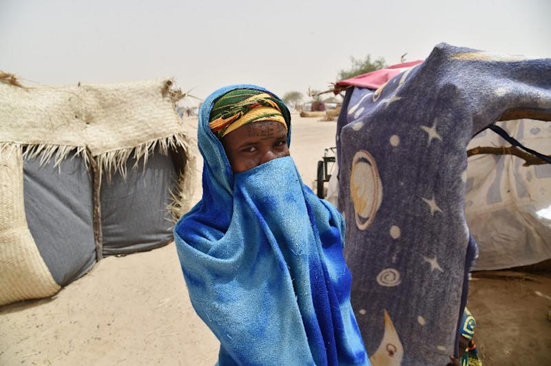 A girl hides herself next to a makeshift tent in a camp in the village of Kidjendi near Diffa, Niger on June 19, 2016 as displaced families fled from Boko Haram attacks in Bosso