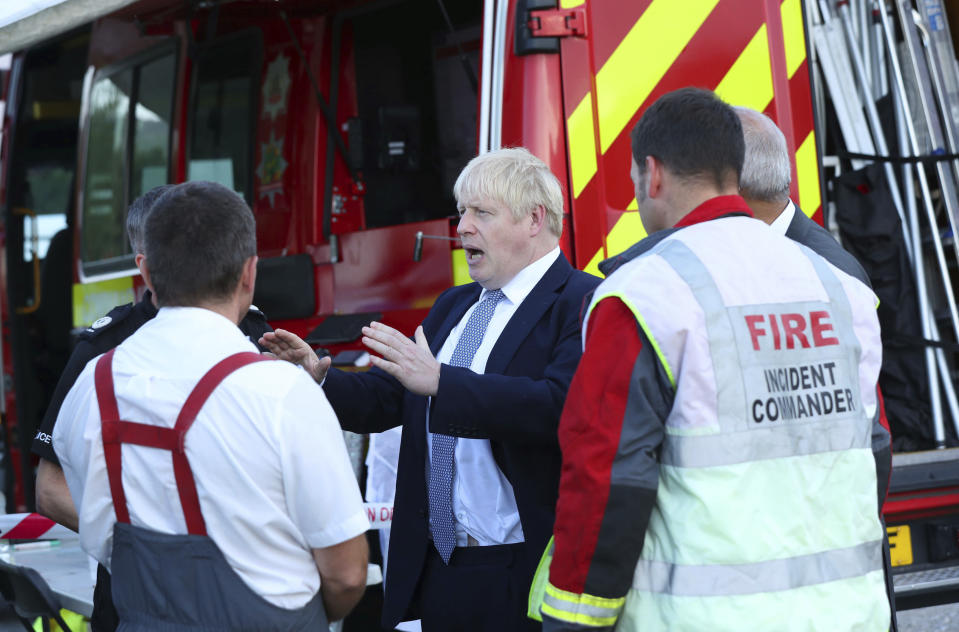 """Britain's Prime Minister Boris Johnson meets with emergency crews during a visit to Whaley Bridge Football Club, after the Toddbrook Reservoir near the village of Whaley Bridge was damaged in heavy rainfall in Derbyshire, England, Friday, Aug. 2, 2019. A British military helicopter dropped sandbags Friday to shore up a reservoir wall as emergency services worked frantically to prevent a rain-damaged dam from collapsing. Engineers said they remain """"very concerned"""" about the integrity of the 19th-century Toddbrook Reservoir, which contains around 1.3 million metric tons (1.5 million (U.S tons) of water. (Yui Mok/Pool photo via AP)"""
