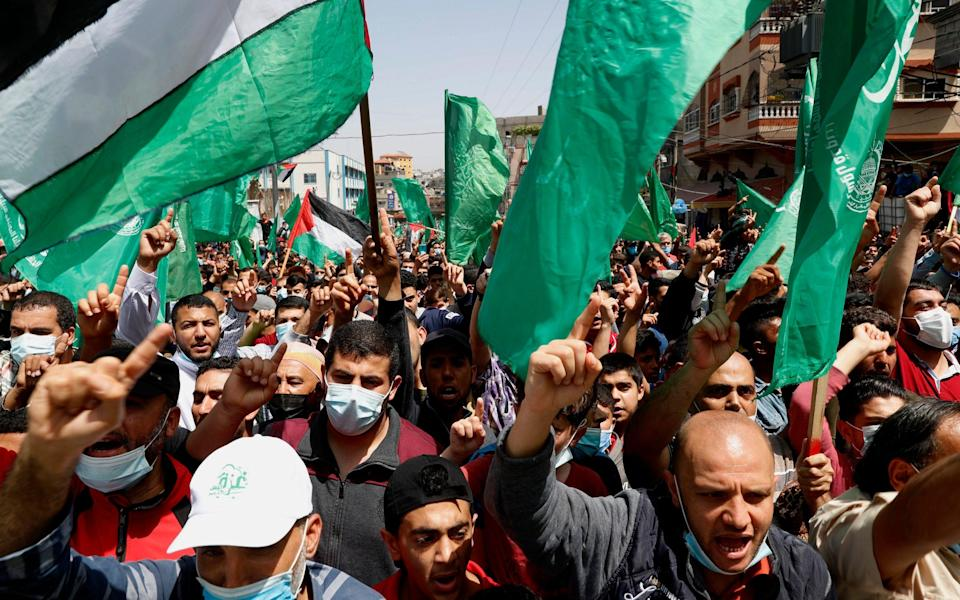 Hamas supporters wave green Islamic flags while chant slogans during a rally in solidarity with fellow Palestinians in Jerusalem and against Palestinian President Mahmoud Abbas decision to postpone Palestinian elections, in Jebaliya refugee camp, Gaza Strip - Adel Hana/AP