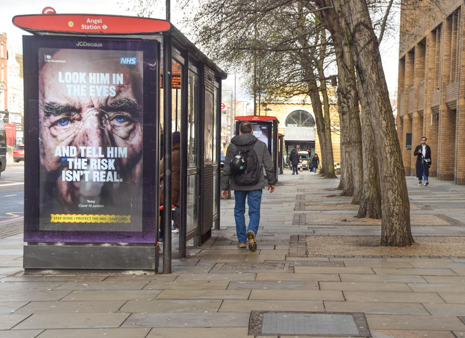 A man walks past a 'Look Him In The Eyes And Tell Him The Risk Isn't Real' coronavirus poster in Angel, London. The covid-19 lockdown remains in place across the UK as the nation continues to struggle with the pandemic. (Photo by Vuk Valcic / SOPA Images/Sipa USA)