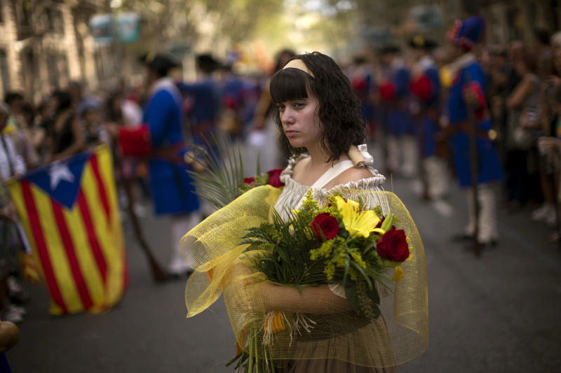 A woman dressed in traditional costume holds flowers to be delivered at the monument of a leader killed during the fall of the city in 1714 in Barcelona, Spain, Tuesday, Sept. 11, 2012. Thousands of people demonstrated in Barcelona on Tuesday to join a rally demanding independence for Catalonia, in north-eastern Spain, on the Catalan national day. (AP Photo/Emilio Morenatti)