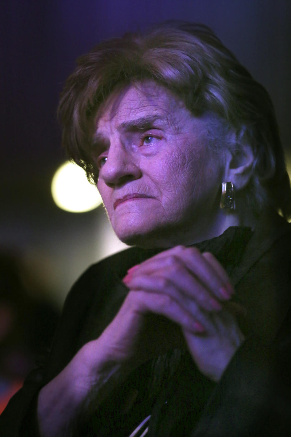 Charlotte Cukier, 90, watches Orthodox Jewish singer Yaakov Shwekey perform at a concert honoring her and dozens of other Holocaust survivors on Monday, June 14, 2021, at the Yeshivah of Flatbush theater in the Brooklyn borough of New York. It was the first large gathering of Holocaust survivors after more than a year of isolation due to the coronavirus pandemic. (AP Photo/Jessie Wardarski)