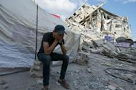 A Palestinian man covers his face as he sits by a tent across from the rubble of buildings destroyed by Israeli strikes in Gaza