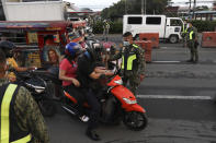 Police officers inspect motorists at a checkpoint during a stricter lockdown as a precaution against the spread of coronavirus on the outskirts of Marikina City, Philippines on Friday, August 6, 2021. Thousands of people jammed coronavirus vaccination centers in the Philippine capital, defying social distancing restrictions, after false news spread that unvaccinated residents would be deprived of cash aid or barred from leaving home during a two-week lockdown that started Friday. (AP Photo/Basilio Sepe)