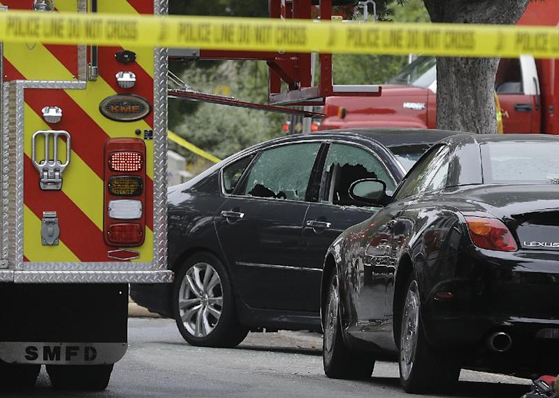 A car with its windows broken stands near where shots were fired near Santa Monica College in Santa Monica, Calif., Friday, June 7, 2013. Two people were found dead in a burned home near the college campus, where someone sprayed a street corner with gunfire, wounding at least three people, authorities said.(AP Photo/Reed Saxon)