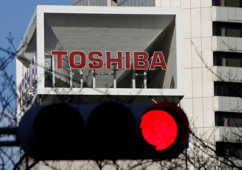 Logo of Toshiba Corp is seen behind a traffic signal at its headquarters in Tokyo
