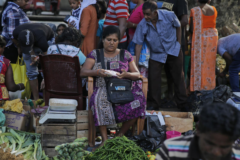 In this July 25, 2019, photo, a Sri Lankan vendor counts money at a market place in Colombo, Sri Lanka. Shocks from deadly suicide bombings on Easter Day in Sri Lanka are reverberating throughout its economy in the worst crisis since the South Asian island nation's civil war ended in 2009. The blasts have devastated Sri Lanka's vital tourism industry, source of jobs for many, and hindering foreign investment. (AP Photo/Eranga Jayawardena)