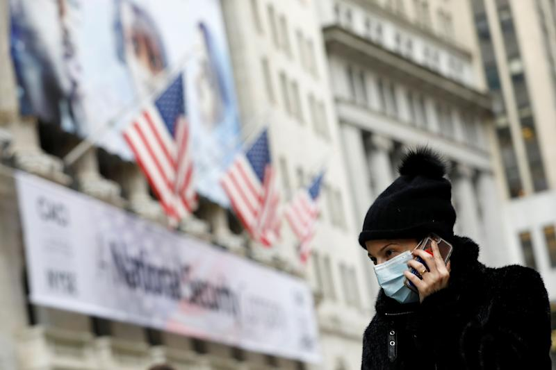 A woman in a surgical mask uses her cellphone after more cases of coronavirus were confirmed in Manhattan, New York City, New York, U.S., March 11, 2020. REUTERS/Andrew Kelly