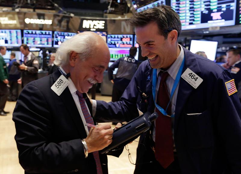 Traders Peter Tuchman, left, and Gregory Rowe share a laugh on the floor of the New York Stock Exchange Wednesday, Sept. 18, 2013. The stock market hit a record high Wednesday after the Federal Reserve's surprise decision to keep its economic stimulus in place. (AP Photo/Richard Drew)