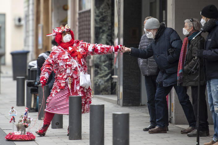CORRECTS THE DATE - Kiki Neumann walks in disguise along the route taken by the carnival parade Rosenmontagszug and delivers candies to spectators in Cologne, Germany, Monday, Feb. 15, 2021. Because of the coronavirus pandemic the traditional carnival parades are canceled. (Marius Becker/dpa via AP)