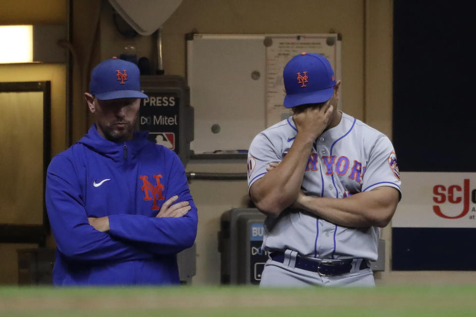 New York Mets manager Luis Rojas, right, is seen in the dugout during the fourth inning of a baseball game against the Milwaukee Brewers on Saturday, Sept. 25, 2021, in Milwaukee. Rojas was let go as manager of the New York Mets on Monday, Oct. 4, 2021, after two losing seasons. The team declined its option on Rojas' contract for 2022, making the announcement a day after finishing third in the NL East at 77-85 in Steve Cohen's first year of ownership. (AP Photo/Aaron Gash)