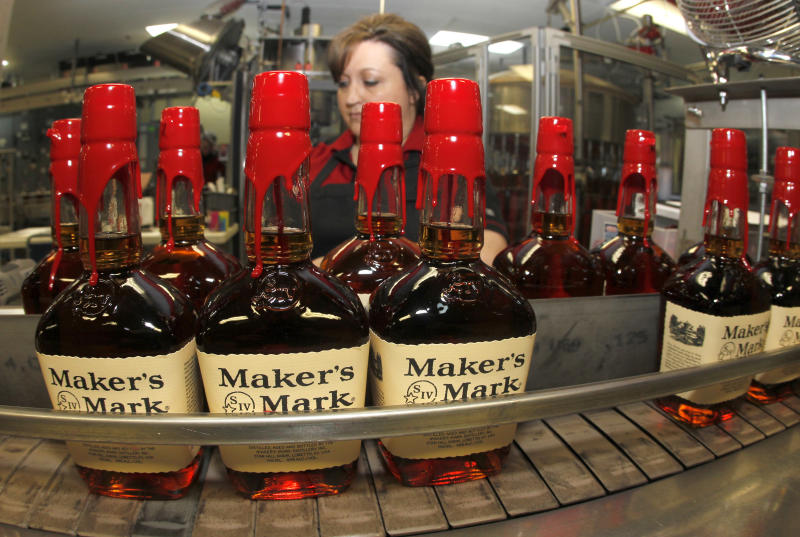 New bottles of Maker's Mark bourbon on the conveyor belt pass by a worker after being hand dipped with their signature red wax, on their way to packaging at the Maker's Mark Distillery plant in Loretto, Kentucky January 23, 2014. (John Sommers II / Reuters)