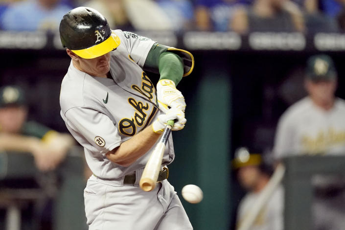 Oakland Athletics' Mark Canha hits an RBI single during the third inning of a baseball game against the Kansas City Royals Wednesday, Sept. 15, 2021, in Kansas City, Mo. (AP Photo/Charlie Riedel)