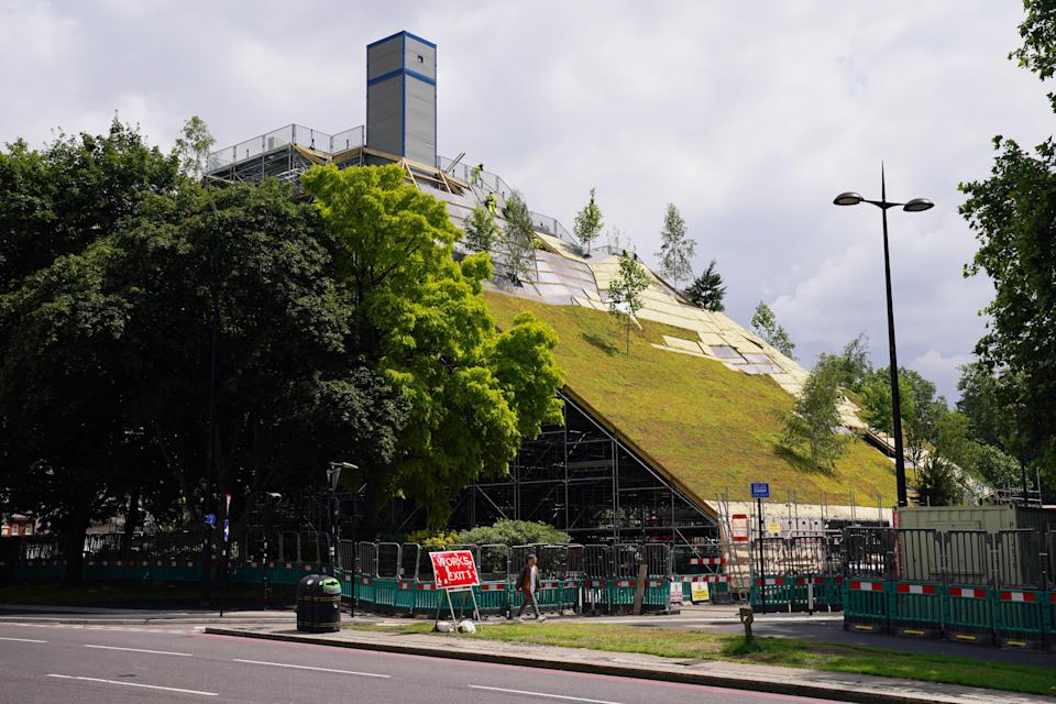 Works continue on the Marble Arch Mound in central London. The summit of the new 25-metre high installation will provide sweeping views of Hyde Park, Mayfair and Marylebone when it opens to the public in July. The artificial hill has been built on a scaffolding base, with layers of soil and plywood forming the mound which has a hollow centre with space for exhibitions and displays. Picture date: Tuesday July 13, 2021.