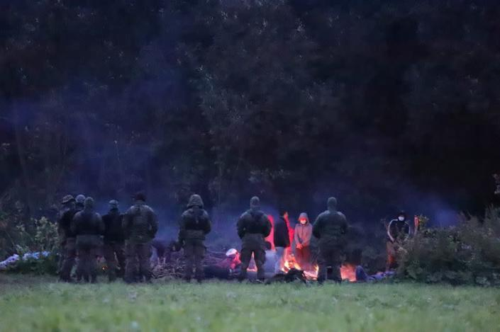 Polish border patrol officers guard a group of migrants who attempted to cross the border between Belarus and Poland near the village of Usnarz Gorny