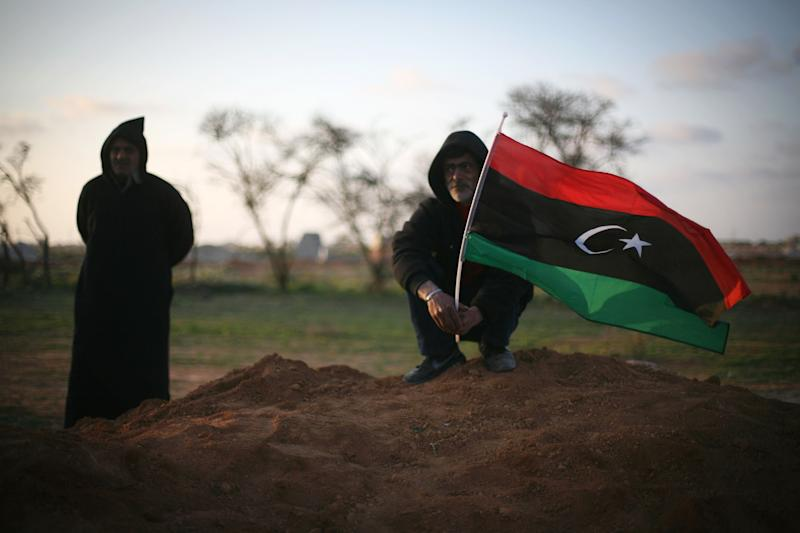 Libyan men, one waving a pre-Gadhafi flag, attend a funeral in Benghazi, Libya, Monday, March 5, 2012 for victims buried in a mass grave. Thousands of mourners gathered Monday in the eastern Libyan city of Benghazi to bury 155 bodies unearthed from a mass grave of people were killed during last year's civil war. It was the largest grave yet to be discovered from the conflict that began as a popular uprising and ended with the capture and killing of Libyan leader Moammar Gadhafi last October.(AP Photo/Manu Brabo)