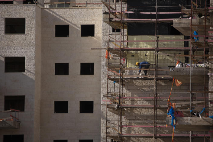 A Palestinian laborer works on a new building in the West Bank Jewish settlement of Efrat, Tuesday, March 16, 2021. Israel went on an aggressive settlement spree during the Trump era, according to an AP investigation, pushing deeper into the occupied West Bank than ever before and putting the Biden administration into a bind as it seeks to revive Mideast peace efforts. (AP Photo/Maya Alleruzzo)