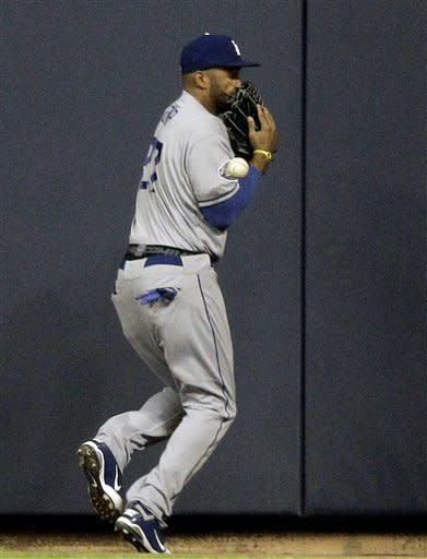 Los Angeles Dodgers center fielder Matt Kemp can't come up with the ball, they went for a triple by Milwaukee Brewers' Jonathan Lucroy during the second inning of a baseball game Tuesday, April 17, 2012, in Milwaukee. (AP Photo/Morry Gash)