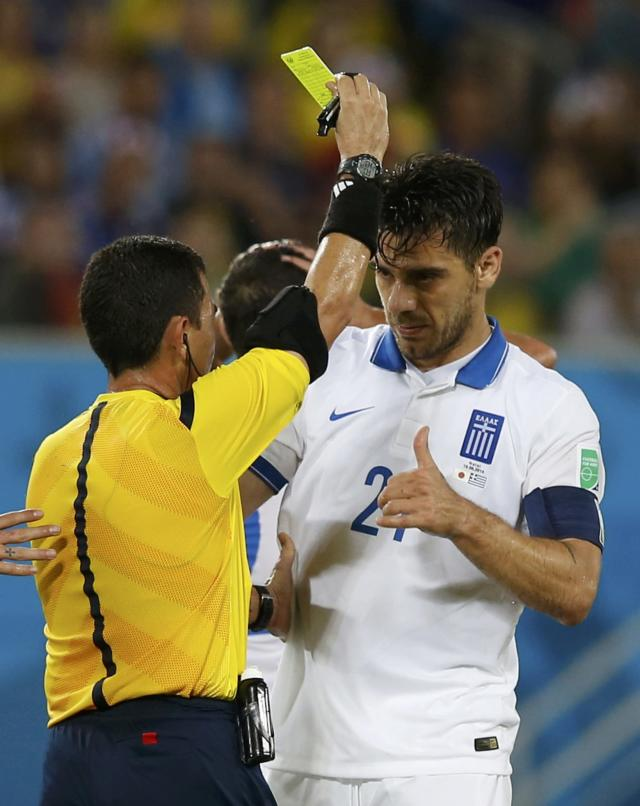 Greece's Kostas Katsouranis (R) is shown a yellow card by referee Joel Aguilar of El Salvador during their 2014 World Cup Group C soccer match against Japan at the Dunas arena in Natal June 19, 2014. REUTERS/Toru Hanai (BRAZIL - Tags: SOCCER SPORT WORLD CUP)
