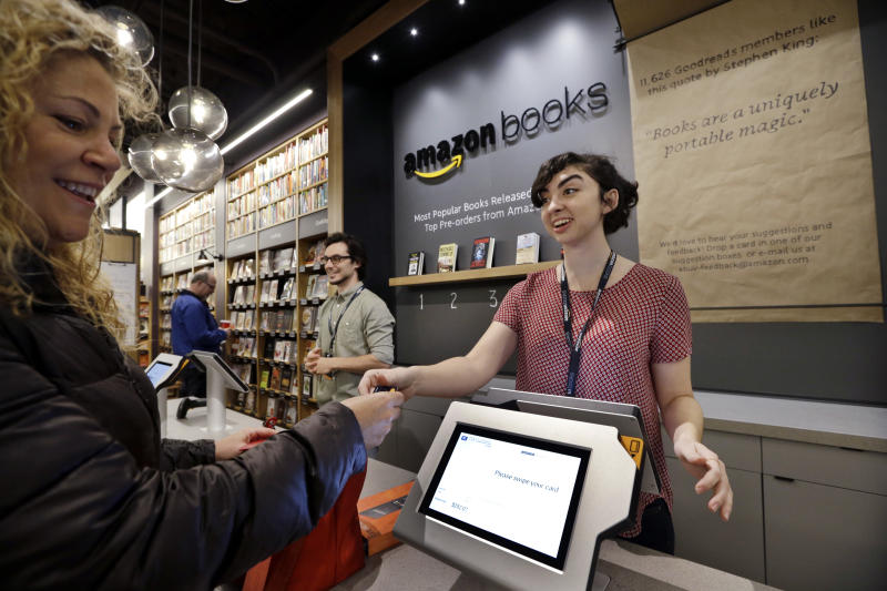 FILE - In this Tuesday, Nov. 3, 2015, file photo, customer Kirsty Carey, left, gets ready to swipe her credit card for clerk Marissa Pacchiarotti, as she makes one of the first purchases at the opening day for Amazon Books, the first brick-and-mortar retail store for online retail giant Amazon, in Seattle. Although Amazon already dominates e-commerce, 90 percent of worldwide retail spending is still in brick-and-mortar stores, according to eMarketer. Amazon has the chance to change retail with automation and data-mining technologies borrowed from e-commerce. (AP Photo/Elaine Thompson, File)