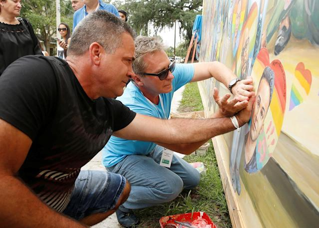 <p>Saul Barrios (L) leaves his handprint on a mural that contains an image of his deceased son Alejandro Barrios Martinez, with the help of artist Yuri Karabash, at the memorial outside the Pulse Nightclub on the one-year anniversary of the shooting in Orlando, Florida, June 12, 2017. (Scott Audette/Reuters) </p>