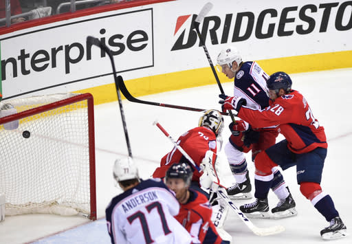 Columbus Blue Jackets left wing Matt Calvert (11) scores a goal past Washington Capitals goaltender Braden Holtby (70) and Jakub Jerabek (28) during overtime in Game 2 of an NHL first-round hockey playoff series, Sunday, April 15, 2018, in Washington. The Blue Jackets won 5-4 in overtime. (AP Photo/Nick Wass)