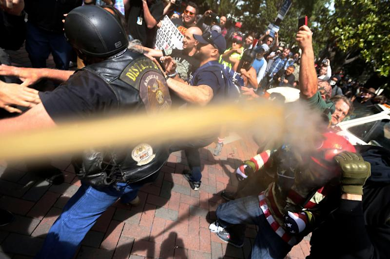 Pepper spray is used as anti and pro-Donald Trump protesters clash during competing demonstrations.  - Credit: Anda Chu/AP
