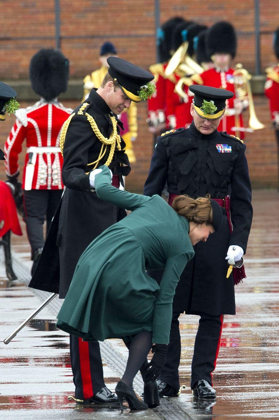 <p>Catherine, Duchess of Cambridge holds on to Prince William as she pulls her heel out of a grate it got stuck in. </p>
