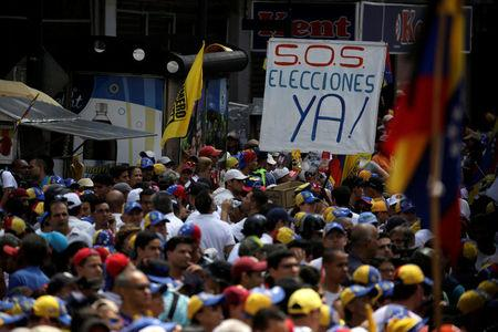 "People participate in an opposition rally in Caracas, Venezuela, April 8, 2017.  The banner reads: ""S.O.S Elections right now!"".  REUTERS/Marco Bello"