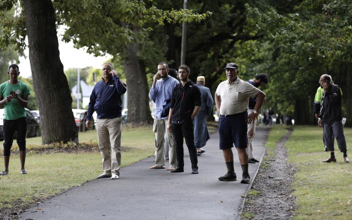 <p>People wait outside across the road outside a mosque in central Christchurch, New Zealand. (AP Photo/Mark Baker) </p>