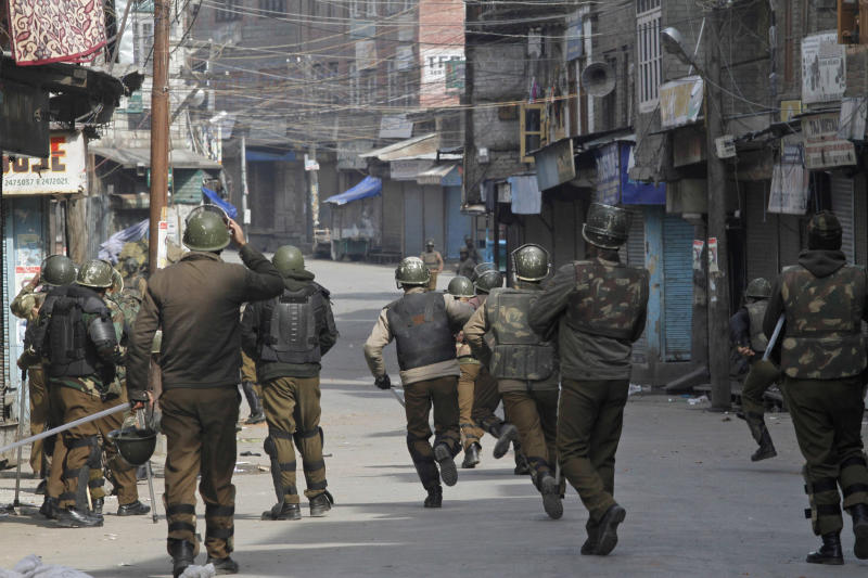 Indian policemen chase Kashmiri Muslim protesters as they try to defy a curfew in Srinagar, India, Monday, Feb. 11, 2013. Sporadic violence left two people dead in Indian-controlled Kashmir despite a curfew that was extended into a third day Monday in the wake of the execution of a Kashmiri man convicted in a deadly 2001 attack on India's Parliament.(AP Photo/ Mukhtar khan)