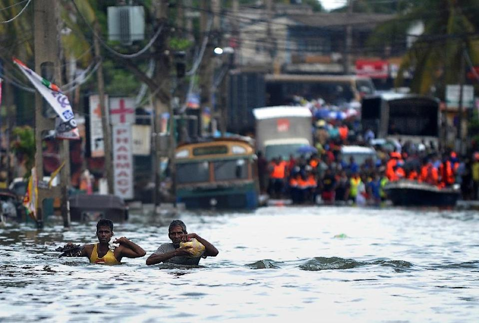 Sri Lankans wade through floodwaters in the Kolonnawa suburb of Colombo on May 20, 2016, following the heaviest rains in a quarter of a century on the island that sparked huge and deadly landslides (AFP Photo/Ishara S.Kodikara)