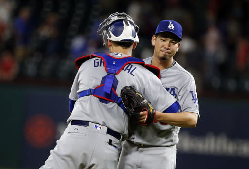 Los Angeles Dodgers catcher Yasmani Grandal (9) congratulates pitcher Kenta Maeda (18) after the Dodgers defeated the Texas Rangers 3-1 during a baseball game Wednesday, Aug. 29, 2018, in Arlington, Texas. (AP Photo/Michael Ainsworth)
