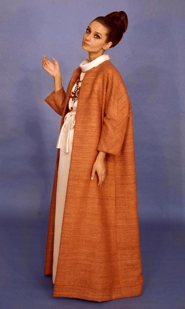 Hepburn wearing a Givenchy burnt orange raw silk and shantung floor-length coat over an off-white floor length dress with tie at waist and cowl neck in a 1964 issue of Vogue.